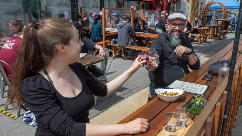 Lawrence L'Oisselle, left, and Eric Deschamps enjoy a restaurant terrasse as they re-open for the first time since last September in Montreal as Quebec begins easing its COVID-19 restrictions on Friday, May 28, 2021. THE CANADIAN PRESS/Ryan Remiorz