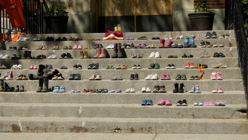 People lay children's shoes on the steps of St. Paul Co-Cathedral in Saskatoon to mourn the 215 children found buried at a former residential school in B.C. (Tyler Barrow/CTV Saskatoon)