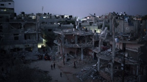 Palestinians walk next to buildings destroyed by airstrikes during an 11-day war between Israel and Hamas, the Palestinian militant group that has ruled Gaza since 2007, Monday, May 31, 2021, in Beit Hanoun, Gaza Strip. (AP Photo/Felipe Dana)
