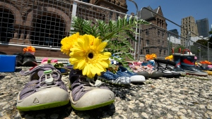 Children's shoes and flowers are shown after being placed outside the Ontario legislature in Toronto on Monday, May 31, 2021. The items were placed as a tribute after the discovery of the remains of 215 children found on the grounds of a former residential school in Kamloops last week. THE CANADIAN PRESS/Frank Gunn
