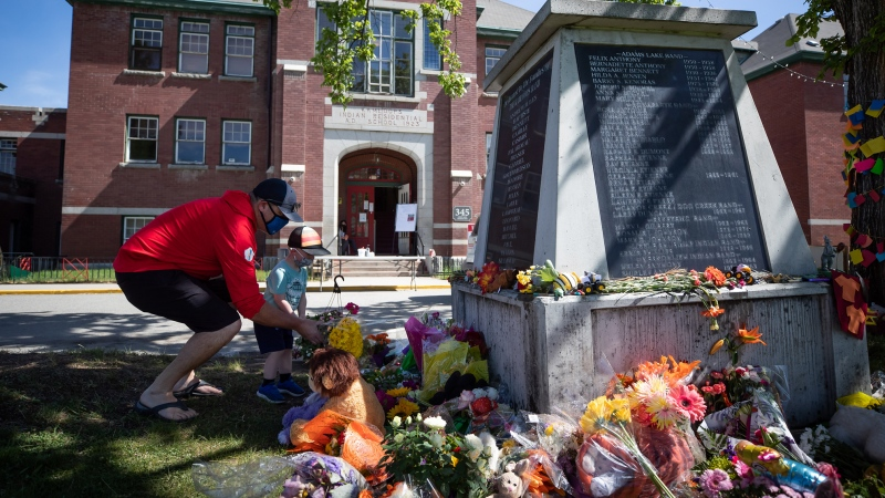 Jaret Hamm and his son John Hamm, 2, place flowers beside a monument outside the former Kamloops Indian Residential School as part of a growing makeshift memorial to honour the 215 children whose remains have been discovered buried near the facility, in Kamloops, B.C., on Monday, May 31, 2021. THE CANADIAN PRESS/Darryl Dyck