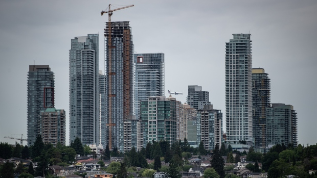 An Air Canada Boeing 787 aircraft arriving from Toronto passes behind condo towers in the Metrotown area of Burnaby, B.C., while on approach to land at Vancouver International Airport, on Sunday, May 30, 2021. (THE CANADIAN PRESS / Darryl Dyck)