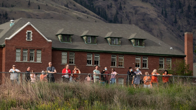 People stand at a fence line outside the former Kamloops Indian Residential School, as they listen to a nearby ceremony that had reached capacity to honour the 215 children whose remains have been discovered buried near the facility, in Kamloops, B.C., on Monday, May 31, 2021. THE CANADIAN PRESS/Darryl Dyck