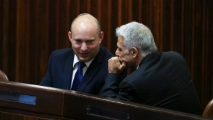Yamina party leader Naftali Bennett, left, smiles as he speaks to Yesh Atid party leader Yair Lapid during a special session of the Knesset, whereby Israeli lawmakers elect a new president, at the plenum in the Knesset, Israel's parliament, in Jerusalem on Wednesday, June 2, 2021. (Ronen Zvulun/Pool Photo via AP)