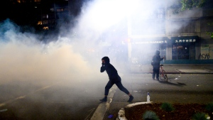 A demonstrator walks through chemical irritants detonated by police in Oakland, Calif., on Friday, May 29, 2020, while protesting the Monday death of George Floyd, a handcuffed black man in police custody in Minneapolis. (AP Photo/Noah Berger)
