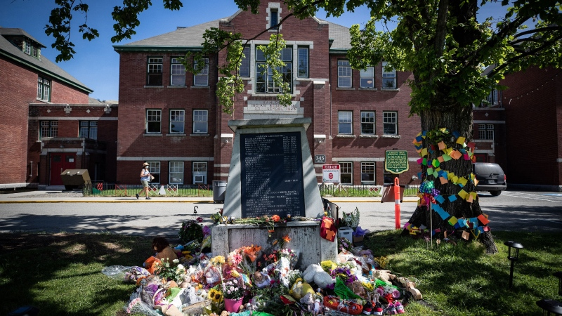 Flowers and cards are left at a makeshift memorial at a monument outside the former Kamloops Indian Residential School, to honour the 215 children whose remains have been discovered buried near the facility, in Kamloops, B.C., on Monday, May 31, 2021. THE CANADIAN PRESS/Darryl Dyck