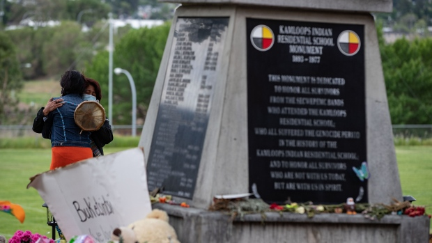 Two women embrace at a monument outside the former Kamloops Indian Residential School where flowers, cards and stuffed animals have been left as part of a growing makeshift memorial to honour the 215 children whose remains have been discovered buried near the facility, in Kamloops, B.C., on Friday, June 4, 2021. THE CANADIAN PRESS/Darryl Dyck