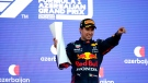 Red Bull driver Sergio Perez of Mexico holds his trophy on the podium after winning the Formula One Grand Prix at the Baku Formula One city circuit in Baku, Azerbaijan, Sunday, June 6, 2021. (Maxim Shemetov, Pool via AP)