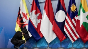 In this Nov. 13, 2018, file photo, a worker adjusts the Brunei Darussalam flag prior the 22nd ASEAN coordinating council meeting on the sidelines of the 33rd ASEAN summit in Singapore. China is hosting foreign ministers from 10 Southeast Asian nations amid heightened competition between Beijing and Washington for influence in the region. (AP Photo/Bernat Armangue, File)