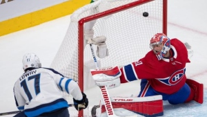 Winnipeg Jets' Adam Lowry (17) scores a goal against Montreal Canadiens goaltender Carey Price (31) during second period NHL Stanley Cup playoff hockey action in Montreal, Sunday, June 6, 2021. THE CANADIAN PRESS/Ryan Remiorz