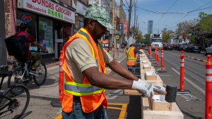 Workers assemble curb lane patio protection for the CaféTO restaurant program, in Toronto, Friday, May 21, 2021. THE CANADIAN PRESS/Frank Gunn