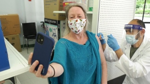 B.C. resident Kelly Fox snaps a selfie as she gets her second dose of the COVID-19 AstraZeneca vaccine at Bonsor Pharmacy in Burnaby, B.C. on June 7, 2021.