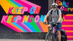A man rides his bicycle past an inspirational mural in Toronto on Tuesday May 25, 2021. THE CANADIAN PRESS/Frank Gunn