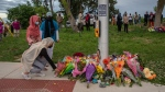 Mourners leave flowers at the site where a family of five was hit by a driver, in London, Ont., Monday, June 7, 2021. (THE CANADIAN PRESS / Brett Gundlock)