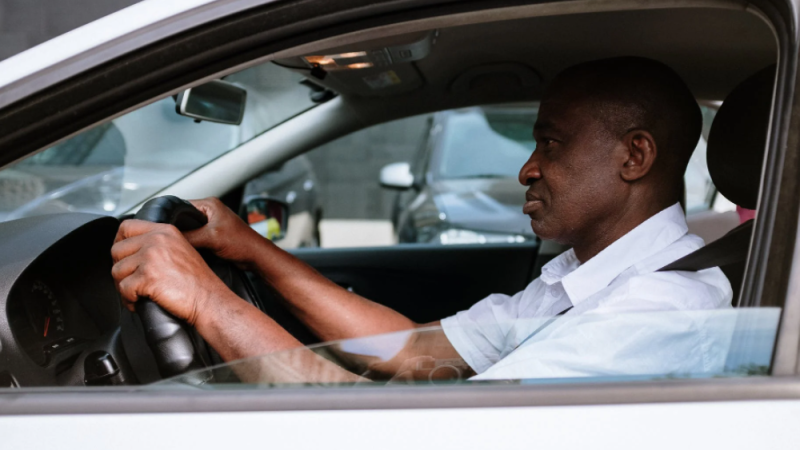 A man is seen driving in a car in this stock image. (Pexels)