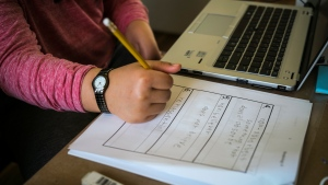 A child writes in their school notebook during a home schooling session in Cremona, Alta., in this file photo from March 23, 2020, THE CANADIAN PRESS/Jeff McIntosh