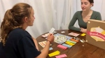 High school student Danika Hindson, right, is playing Breadwinner, a board game she and friend Valentina Mounzer created. The pair won a national challenge aimed at teaching youth about finances. (Photo courtesy / Danika Hindson and Valentina Mounzer)
