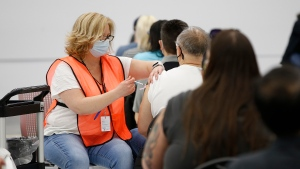 People receive their vaccinations from Karen Balzer at Manitoba's COVID-19 vaccination centre in a soccer complex in north Winnipeg, Friday, May 7, 2021. THE CANADIAN PRESS/John Woods
