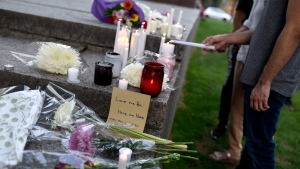 A mourner lights a candle at a memorial for the four family members who were killed in a vehicle attack that police say was motivated by anti-Muslim hate, in London, Ont., in Ottawa, on Tuesday, June 8, 2021. THE CANADIAN PRESS/Justin Tang