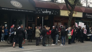 A group of people protest COVID-19 restrictions outside Corduroy restaurant in Vancouver, B.C., on April 23, 2021.