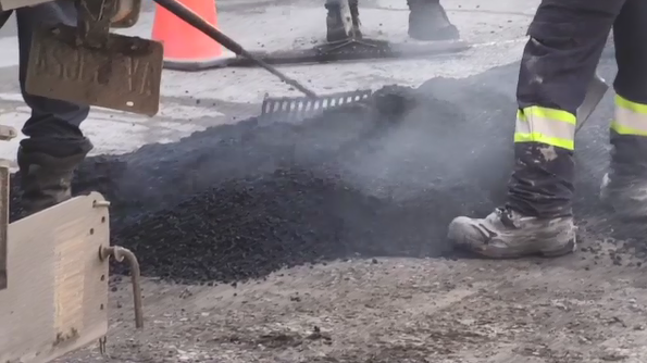 Construction workers filling a pothole