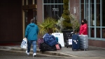 A person walks inside with a shopping bag from a nearby mall as a traveller waits to check-in at a government-authorized COVID-19 quarantine hotel in Richmond, B.C. on Sunday, February 28, 2021. Travellers arriving in Canada are required to reserve a government-authorized hotel for three nights and stay at the hotel while awaiting the results of a COVID-19 test done upon arrival in the country. THE CANADIAN PRESS/Darryl Dyck