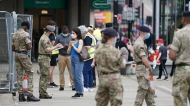 Members of the Armed Forces speak to people, outside a mobile COVID-19 vaccination centre outside Bolton Town Hall, in Bolton, England, Wednesday, June 9, 2021, where case numbers of the Delta variant first identified in India have been relatively high. (Peter Byrne/PA via AP)