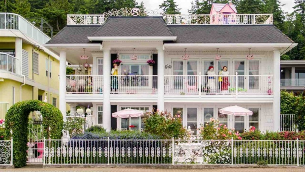 Life-sized dolls are seen on the upstairs balcony of a whimsical home in White Rock, B.C., that's listed for sale for just under $4 million. (Cindy Russell/eXp Realty)