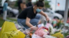 A woman arranges flowers at the scene of Sunday's hate-motivated vehicle attack in London, Ont. on Tuesday, June 8, 2021, in honour of the four members of a Muslim family that died and the youngest boy who is in hospital. THE CANADIAN PRESS/ Geoff Robins