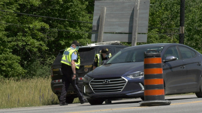 Ontario Provincial Police speak with a Quebec motorist at the Ontario-Quebec crossing along Highway 148 in Pembroke. (Dylan Dyson/CTV News Ottawa)