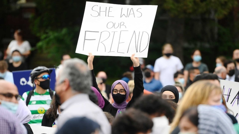 A young woman holds a sign as she attends a vigil outside the London Muslim Mosque for the victims of the deadly vehicle attack on five members of the Canadian Muslim community in London, Ont., on Tuesday, June 8, 2021. THE CANADIAN PRESS/Nathan Denette