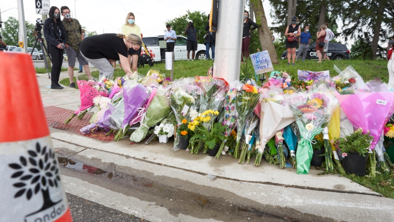 Mourners place flowers at the scene of a hate-motivated vehicle attack in London, Ont. on Tuesday, June 8, 2021, which left four members of a family dead and their nine-year-old son in hospital. THE CANADIAN PRESS/ Geoff Robins