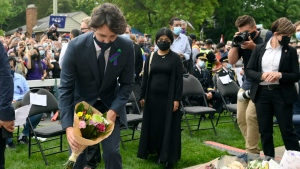Prime Minister Justin Trudeau places flowers at a vigil for the victims of the deadly vehicle attack on five members of the Canadian Muslim community in London, Ont., on Tuesday, June 8, 2021. Four of the members of the family died and one is in critical condition. Police have charged a London man with four counts of murder and one count of attempted murder. THE CANADIAN PRESS/Nathan Denette