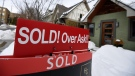 A for sale sign outside a home indicates that it has sold for over the asking price, in Ottawa, on Monday, March 1, 2021. (THE CANADIAN PRESS / Justin Tang)