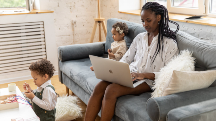 A woman works on her laptop while her children play in this stock image (Pexels/Ekaterina Bolovtsova)
