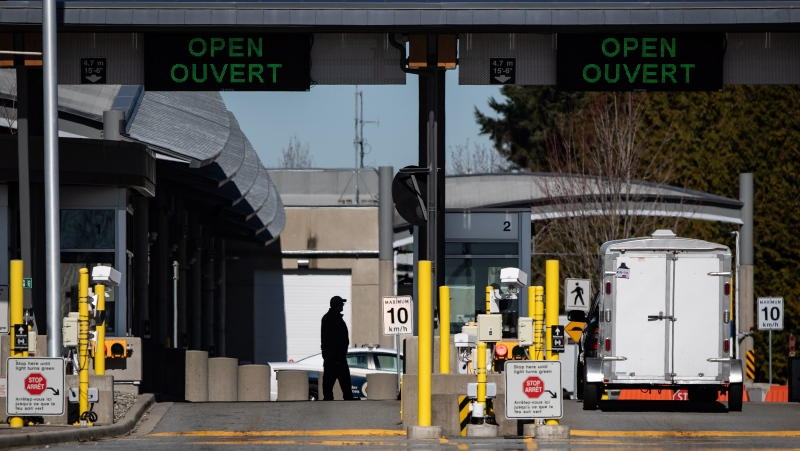 A Canada Border Services Agency officer is silhouetted at the Douglas-Peace Arch border crossing, in Surrey, B.C., on Monday, March 16, 2020. THE CANADIAN PRESS/Darryl Dyck