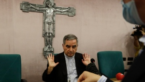 FILE - In this Sept. 25, 2020 Cardinal Angelo Becciu talks to journalists during a press conference in Rome. Italy's financial police said Wednesday, Oct. 14, 2020 that a Sardinian woman, Cecilia Marogna, said to be close to one of the Holy See's most powerful cardinals, Becciu, before his downfall, was arrested in Milan, northern Italy, late Tuesday on an international warrant issued by the Vatican City State. (AP Photo/Gregorio Borgia, file)