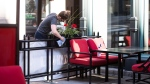A staff member prepares the patio for Friday's reopening at a downtown Ottawa pub, as Ontario prepares to enter the first phase of its reopening plan amidst the third wave of the COVID-19 pandemic, on Thursday, June 10, 2021. (Justin Tang/THE CANADIAN PRESS)