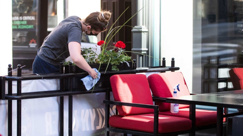 A staff member prepares the patio for Friday's reopening at a downtown Ottawa pub, as Ontario prepares to enter the first phase of its reopening plan amidst the third wave of the COVID-19 pandemic, on Thursday, June 10, 2021. THE CANADIAN PRESS/Justin Tang