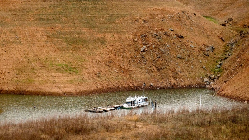 Surrounded by dry hillsides, a houseboat floats on Lake Oroville on Saturday, May 22, 2021, in Oroville, Calif. At the time of this photo, the reservoir was at 39 percent of capacity and 46 percent of its historical average.  (AP / Noah Berger)
