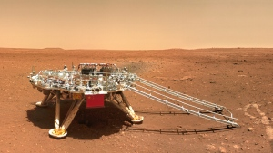 In this image released by the China National Space Administration (CNSA) on Friday, June 11, 2021, the landing platform with a Chinese national flag and outlines of the mascots for the 2022 Beijing Winter Olympics and Paralympics on Mars is seen from the rover Zhurong. (CNSA via AP)