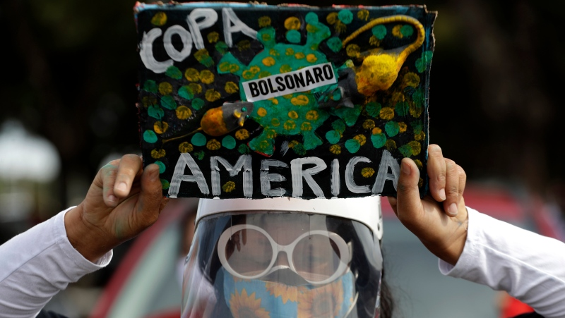 A woman holds a sign to protest Brazil's decision to hold the Copa America in Brasilia, Brazil, Sunday, June 6, 2021. Brazil accepted hosting the the Copa America after the original co-hosts were dropped, Colombia due to political protests and Argentina for rising of COVID-19 cases. (AP Photo/Eraldo Peres)