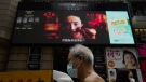 """In this Thursday, Sept. 17, 2020, file, People walk past a huge TV screen showing movie listings """"along a downtown street in Hong Kong. (AP Photo/Vincent Yu, File)"""