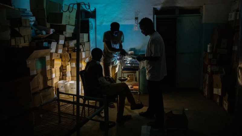 Surgeon and doctor-turned-refugee, Dr. Tewodros Tefera, checks a Tigrayan refugee inside the Sudanese Red Crescent clinic, at Hamdayet Transition Center near the Sudan-Ethiopia border, eastern Sudan, on March 23, 2021.  (AP Photo/Nariman El-Mofty)