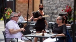 A server brings an order to patrons on a steakhouse's outdoor patio in Ottawa on the first day of Ontario's first phase of re-opening amidst the third wave of the COVID-19 pandemic, on Friday, June 11, 2021. (Justin Tang/THE CANADIAN PRESS)