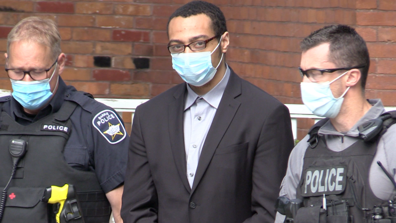With his hands and ankles in cuffs, Dyrrin Daley was led inside the William Street home on Fri. June 11, 2021, where the Crown attorney said he brutally murdered James and Nick Pasowisty four years ago. (Mike Arsalides/CTV News)