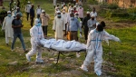Municipal workers prepare to bury the body of a person who died of COVID-19 in Gauhati, India, Sunday, April 25, 2021. (AP Photo/Anupam Nath)