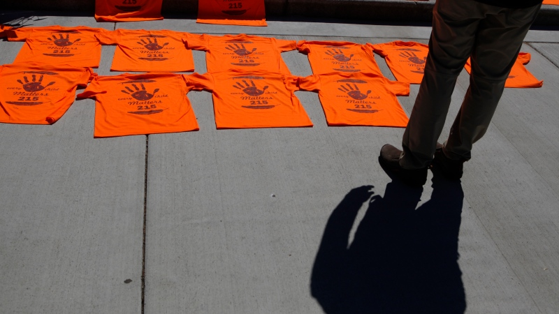 A man looks over the orange shirts, shoes, flowers and messages are displayed on the steps outside the legislature in Victoria, B.C., on Tuesday, June 8, 2021 following a ceremony hosted by the Songhees and Esquimalt First Nations in honour of the 215 residential school children whose remains have been discovered buried near the facility in Kamloops, B.C. THE CANADIAN PRESS/Chad Hipolito