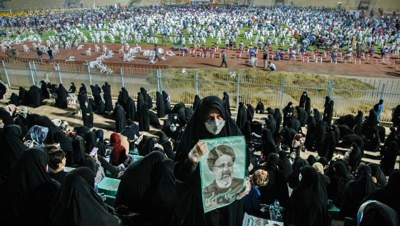 In this Wednesday, June 9, 2021, photo, a supporter of the presidential candidate Ebrahim Raisi, currently judiciary chief, hold posters of him during a campaign rally at the Takhti Stadium in Ahvaz, Iran. (Amin Nazari/ISNA via AP)