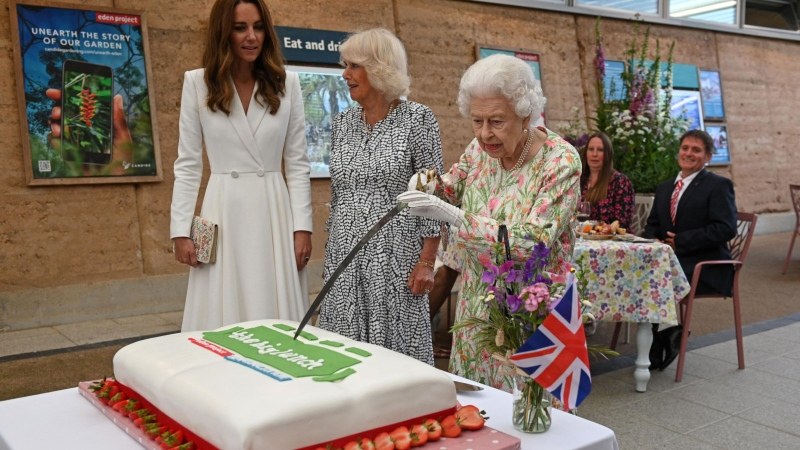 Queen Elizabeth II showed off her sword skills Friday cutting a cake at a lunch organized by educational charity Eden Project. (Oli Scarff/AFP/Pool/Getty Images/CNN)